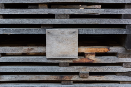 tannins: Oak planks for wine barrels stacked in piles for elution of tannins on the open air, with a blank plywood sign, on which can be located your text Stock Photo