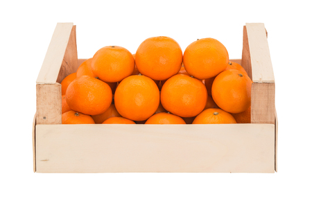 Ripe, juicy tangerines in a wooden box stacked as pyramid. Front view Stock Photo