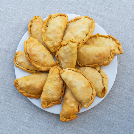 Fresh, crispy, puff pies on a white plate. View from above