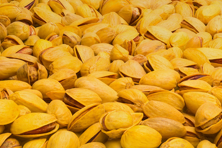 Pistachios are yellow fried with turmeric. Lying in perspective on the horizontal plane.