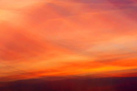 Blurry background of dramatic colorful sky. Burning clouds at sunset view. Cloud pattern texture in yellow, orange, purple colors backgrounds.
