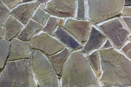 Wall clad in colorful flagstone with wide cement joints