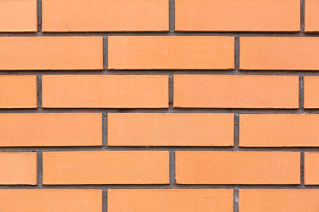 Detailed view of a orange brick wall with wide cement seams. Building background 写真素材