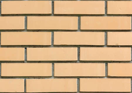 Detailed view of a light yellow brick wall with wide cement seams. Construction background