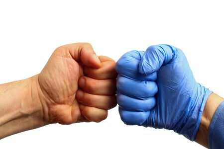 Doctor's hand in a medical glove and patient's hand clenched in fists, on a white background, isolated. Friendship concept Stockfoto