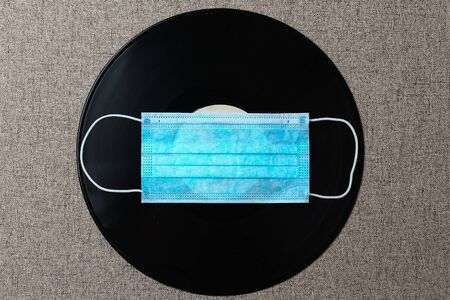 Vinyl audio record and medical surgical mask, abstract concept of nostalgia for music and concerts under quarantine and self-isolation due to the pandemic of Covid-19 (coronavirus)