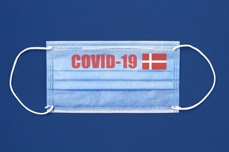 Medical mask and text or inscription Covid-19. Coronavirus pandemic concept. Flag of Denmark.