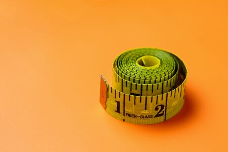 Inch and centimeter tape on a trendy in advertising orange background with copy space for an inscription or text