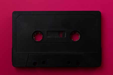 Black audio cassette close-up on a pink background