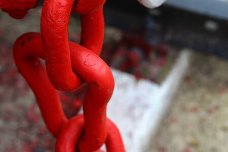 Link element of a chain of red color, massive metal, background