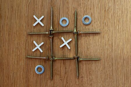 Resourcefulness and creativity in the organization of the game. Tic tac toe. Improvised attributes: screws, washers and crosses for laying tile