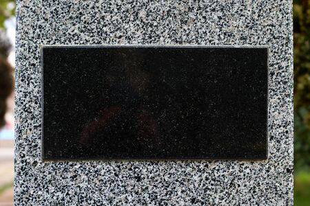 Black marble tablet on gray granite, blank for text or inscription