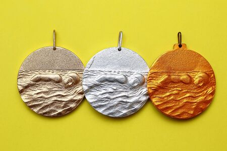 Gold, silver and bronze medals on a fashionable yellow background Stock Photo