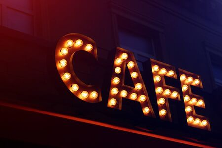 Sign from light bulbs with the word CAFE in the night city, toned