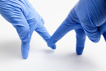 Hands in medical gloves metaphorically depict people, abstract concept of greeting each other with a touch of the feet during the COVID-19 pandemic