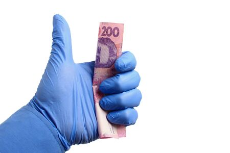 A hand in a medical glove holds Ukraine state money, hryvnia, on a white background isolated. The concept of international financial assistance