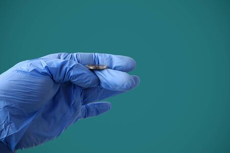 A doctor in a medical glove tosses a coin against a background of Marrs green. Symbol of choice