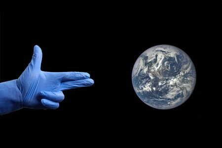 A hand in a medical glove metaphorically depicts a gun aimed at firing on planet Earth.