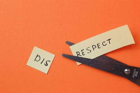 The inscription on the sticker DISRESPECT cut in half on an orange background
