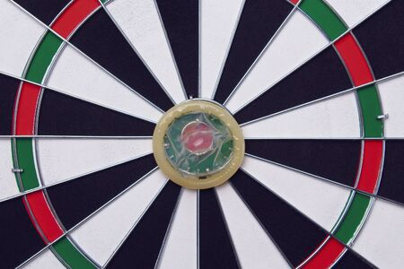 Unpacked condom on the background of a dartboard target darts toned Stock Photo