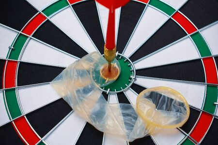Unpacked condom broken dart on a background of a target for darts, toned