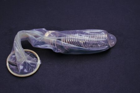 Metal coins in an unpacked condom on a black background, toned