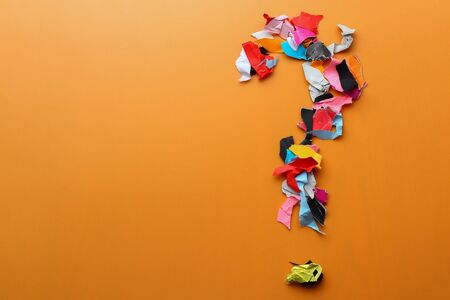 Question mark made from pieces of torn colored paper, abstract background with copyspace for text