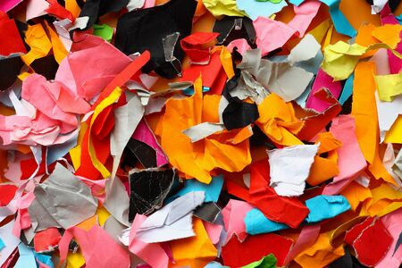 Torn small pieces of multi-colored paper, bright colorful background