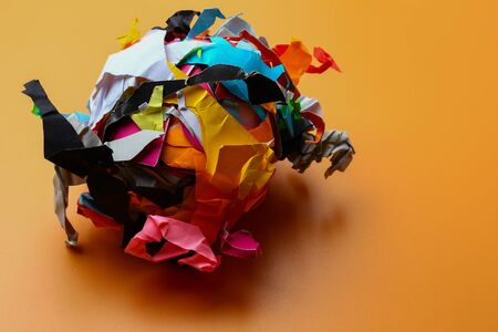 Crumpled torn pieces of colored paper, abstract concept, background, symbolic metaphor