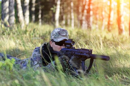 The sniper lies in wait, looks through the scope, toned