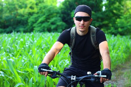 Young male cyclist in nature toned symbolic abstract background