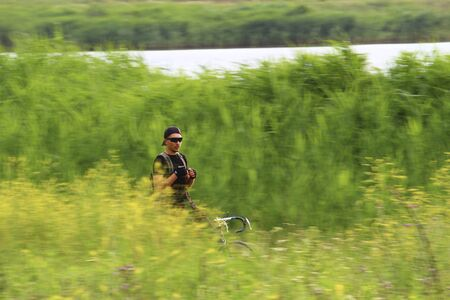 Young male cyclist in nature, toned. Motion blur . Riding a bike without hands. Soft focus. Blurred.