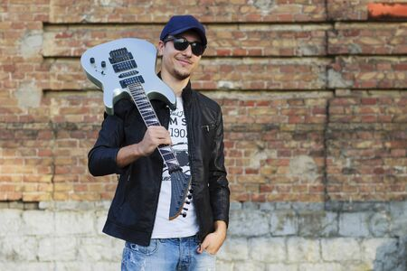 Young handsome guy with a guitar on his shoulder, the blurry background of a brick wall