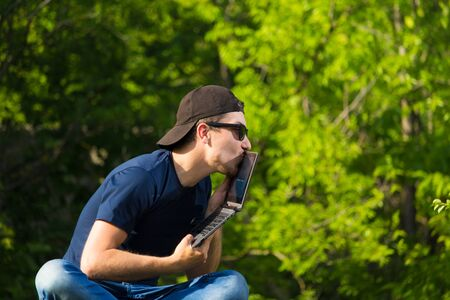A man kisses a laptop camera while sitting in nature