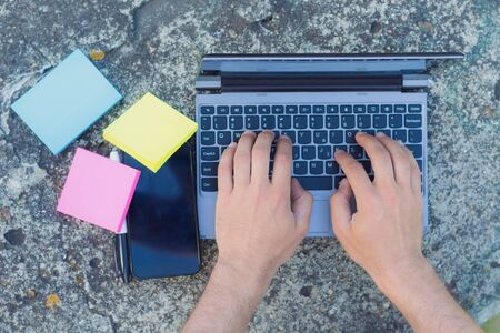 An employee of an online store works on a concrete city curb. Hands, laptop keyboard, smartphone, marker and color stickers, toned Archivio Fotografico