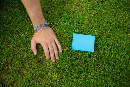 A hand tied to a color sticker with a metal chain, on a background of grass lawn, toned, with copy space for an inscription or text. Concept of addiction, commitment and affection, trap.