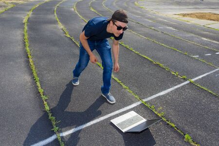 Freelancer with a laptop at the start of the running track of the stadium. The concept of starting a business and freelancing a successful and quick start. Toned. Copy space for text or inscription