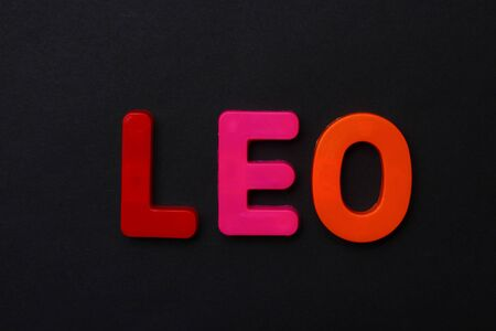 Leo text. Zodiac sign written in bright multi-colored cheerful letters on a black dramatic background. Low dark key. Horoscope Theme