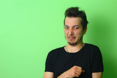Expressive young man or guy on a light green background. Emotion of disgust Imagens