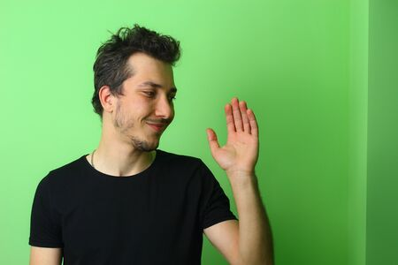 Young man or guy on a light green wall background. Emotion of Guilt and Forgiveness