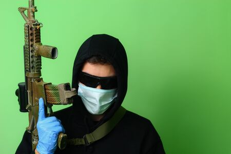 Young male gangster or criminal in a medical surgical mask and sunglasses dressed in black clothes with a hood holds an automatic assault weapon