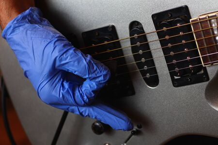 A musician plays with gloves on a musical instrument in an audio studio. The life of a guitarist in the realities of covid-19 pandemic