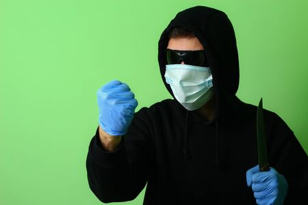 Young male gangster or criminal in a medical surgical mask and sunglasses dressed in black clothes with a hood holds a knife in his hand 写真素材