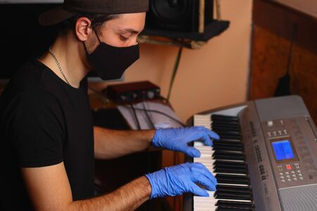 A musician plays with gloves on a musical instrument in an audio studio. The life of a pianist in the realities of Covid-19 pandemic.