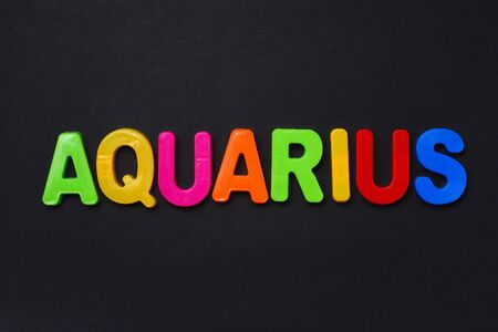 Aquarius text. Zodiac sign written in bright multi-colored cheerful letters on a black dramatic background. Low dark key. Horoscope Theme