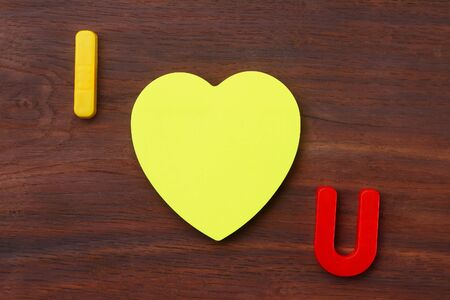 Letters I and U with a blank symbolic heart shaped sticker. Short Message I love you. Background 스톡 콘텐츠