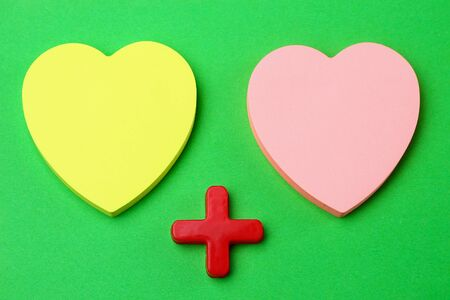 Two blank heart shaped stickers with plus sign. Creative symbolic background on the theme of love