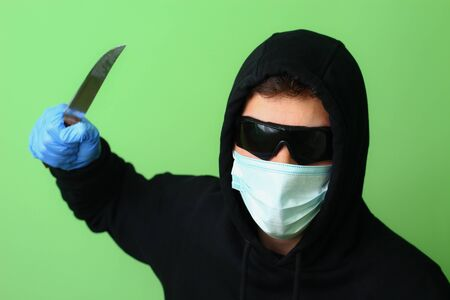 Young male gangster or criminal in a medical surgical mask and sunglasses dressed in black clothes with a hood holds a knife in his hand Фото со стока