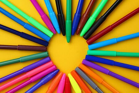 Multi-colored markers form a heart-shaped frame for lettering or inscription. Background with copyspace for text