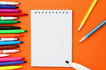 Open blank checked notebook and many multi-colored markers on an orange background. Mockup with copyspace.